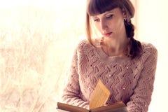 女孩在窗口附近的阅读书。 免版税库存图片