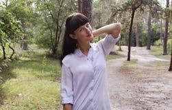 女孩在站立在森林背景的公园 免版税库存图片