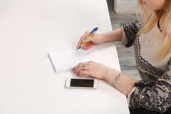 女孩在笔记本写某事 免版税库存图片