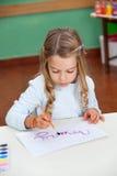 女孩在纸的绘画名字在书桌 免版税库存照片
