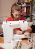 女孩在缝纫机缝合 免版税图库摄影