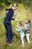 女孩在美丽的公园,有网的捉住蝴蝶,微笑和笑,嬉戏的心情,幼稚胡闹 免版税库存照片