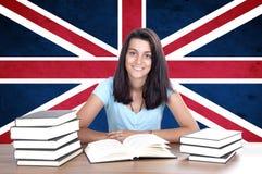 女孩在背景的学生个人计算机与英国旗子 免版税库存图片