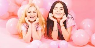 女孩在腹部在气球附近,桃红色背景放置 姐妹或最好的朋友睡衣的在少女睡衣派对 闲话 库存图片