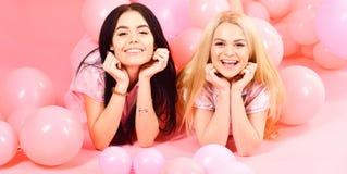 女孩在腹部在气球附近,桃红色背景放置 姐妹或最好的朋友睡衣的在少女睡衣派对 闲话 免版税库存图片