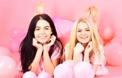 女孩在腹部在气球附近,桃红色背景放置 闲话概念 白肤金发和深色在微笑的面孔获得乐趣在 免版税图库摄影