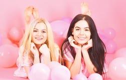 女孩在腹部在气球附近,桃红色背景放置 闲话概念 白肤金发和深色在微笑的面孔获得乐趣在 免版税库存照片