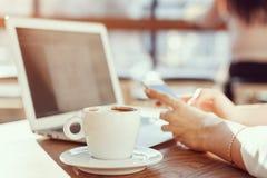 女孩在膝上型计算机的一个咖啡馆工作并且喝咖啡 免版税图库摄影