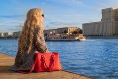 女孩在船坞坐并且调查距离 由河的温暖的秋天天气 免版税图库摄影