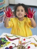 女孩在艺术课的手指画法 库存照片