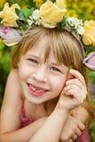 女孩在花圈特写镜头的6岁 微笑 乳齿掉下来 库存图片