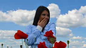 女孩在花的鸦片领域微笑着 免版税库存图片
