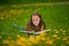 女孩在草甸读一本书 免版税库存照片