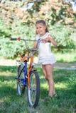 女孩在草的夏天公园在自行车旁边 库存图片