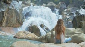 女孩在莲花姿势坐反对瀑布和岩石 股票视频