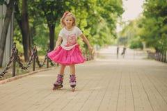 女孩在蓬松桃红色裙子rollerblading 免版税库存图片