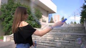 女孩在街道做肥皂泡以台阶为背景 股票录像