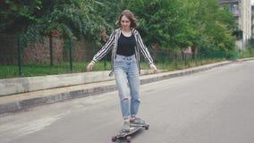 女孩在街道,慢动作的骑马滑板Longboard 股票录像