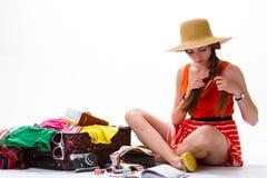 女孩在被过度充填的手提箱附近坐 免版税库存图片