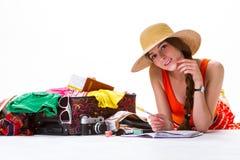 女孩在被过度充填的手提箱附近放置 库存图片