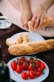 女孩在西红柿、白色咖啡和篮子旁边切了在板材的长方形宝石 免版税库存照片