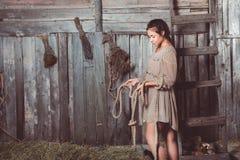 女孩在谷仓在她的手上的拿着绳索 免版税库存照片