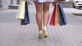女孩在购物以后运载不同的颜色包裹与购物的 慢的行动 股票视频