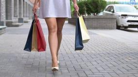 女孩在购物的步行运载不同的颜色包裹与购物的沿着向下街道以后 慢的行动 HD 股票录像