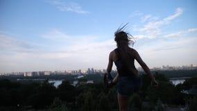 女孩在起动angoo跃迁跳,她回到在她前面的照相机俯视城市 r 影视素材