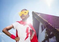 女孩在超级英雄在她的站立反对房子的腰部的服装手上在背景中 免版税图库摄影