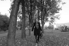 女孩在路在神奇森林背景中去墙纸的 一场雾的奇怪的森林与红色叶子 神秘主义者 免版税库存图片