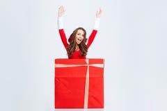 女孩在跳出当前箱子的圣诞老人服装 免版税图库摄影