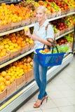 女孩在选择果子的市场上递柠檬 免版税库存图片