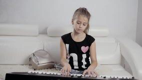女孩在钢琴的键盘的` s手 女孩弹钢琴,钢琴的关闭 在钢琴的白色钥匙的手 股票视频