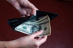女孩在钱包投入美元 免版税库存图片