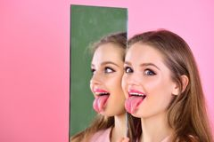 女孩在镜子的展示舌头作为多面的个性 秀丽和方式 美发师沙龙和构成概念 免版税库存照片