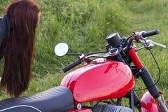 女孩在镜子站立近的葡萄酒摩托车并且看户外 免版税库存图片