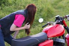 女孩在镜子站立近的葡萄酒摩托车并且看户外 图库摄影