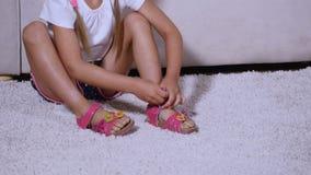 女孩在长沙发附近穿戴桃红色凉鞋 影视素材