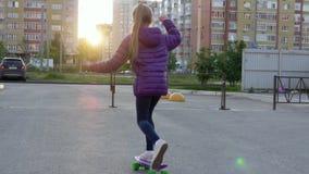 女孩在长的委员会的少年溜冰板运动在城市街道上,当平衡日落时 少女在街道上的骑马滑板 影视素材