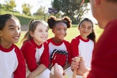 女孩在队杂乱的一团的棒球队听教练的 免版税图库摄影