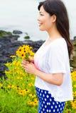 女孩在雏菊向日葵领域站立在海滩附近 库存图片