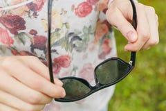 女孩在雨中拿着太阳镜他的手 库存照片