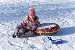 女孩在雪坐与冬天玩具的一个明亮的晴天 免版税图库摄影