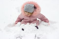 女孩在雪坐,使用与在夜落的新鲜的雪 免版税库存图片