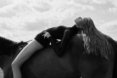 女孩在领域的一匹马弯曲的车手谎言 妇女的时尚画象和母马是马在天空的村庄 库存照片