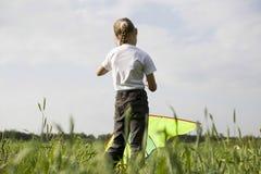女孩在领域的飞行风筝 库存照片
