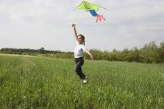 女孩在领域的飞行风筝 库存图片