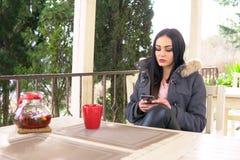 女孩在餐馆使用智能手机午餐 免版税库存图片