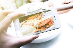 女孩在餐馆使用智能手机,为食物照相 库存照片
